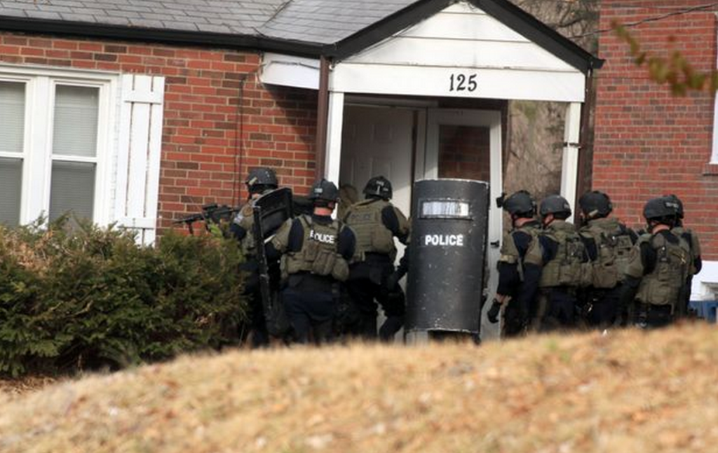 St. Louis County SWAT team swarm a house in Ferguson, Thursday morning, March 12, 2015, following the midnight shooting of two police officers in Ferguson