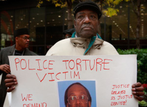 Aaron Cheney demonstrates outside the federal courthouse where former Chicago Police Commander Jon Burge was attending a hearing on charges he obstructed justice and committed perjury for lying while under oath during a 2003 civil trial about decades-old Chicago police torture allegations October 27, 2008 in Chicago, Illinois. Burge cannot be charged for the torture of suspects because the federal statute of limitations for the crime has expired.  (Photo by Scott Olson/Getty Images)
