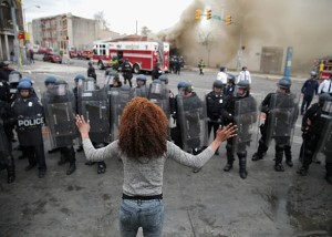 A woman faces a line of Baltimore police officers in riot gear during protests following the funeral of Freddie Gray on April 27, 2015, in Baltimore.