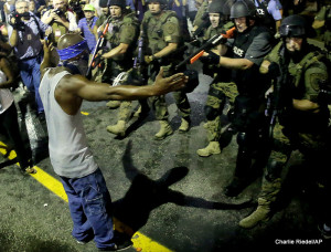 In this Aug. 20, 2014 file photo police arrest a man as they disperse a protest against the shooting of Michael Brown in Ferguson, Mo.