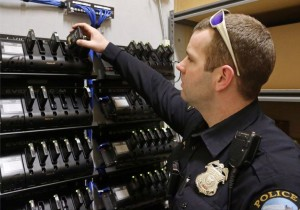 Duluth, Minn., police officer Dan Merseth demonstrates the docking procedure for police body cameras at police headquarters. Duluth initially received 84 cameras and charging bays for less than $5,000 from camera maker Taser International, but its three-year contract and licensing agreement for data storage cost about $78,000.