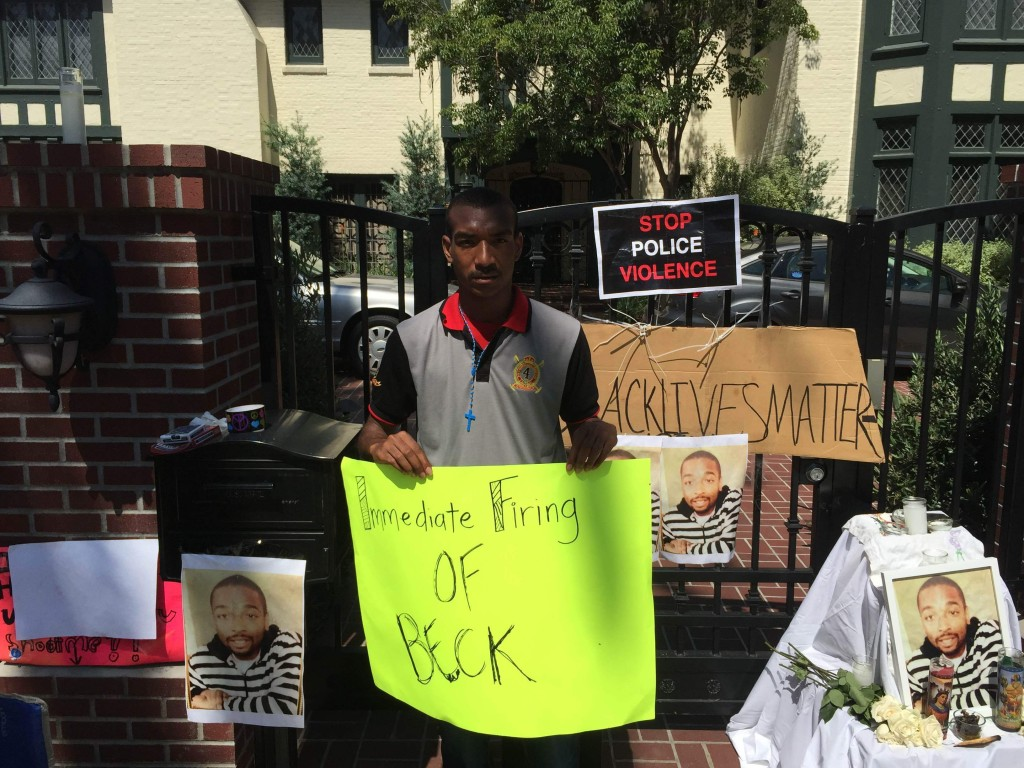 Dedric Kennedy stands in front of Garcetti's mayoral residence holding a sign protesting the fatal shooting of Ezell Ford.