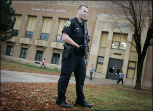 Green Bay Police Officer Matt Secor stands guard outside Washington Middle School during dismissal after a shooting at nearby 1315 Crooks Street, Thursday afternoon, Nov. 19, 2009.