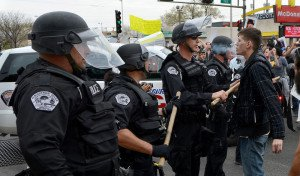 A protester blows smoke into the face of an Albuquerque Police Officer at Central and Yale during a free flowing protest march against APD on Sunday, March 30, 2014.(Greg Sorber/Albuquerque Journal)